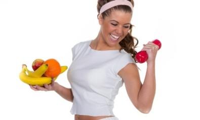 Lachende junge Frau mit Früchten und einer roten Hantel trainiert begeistert